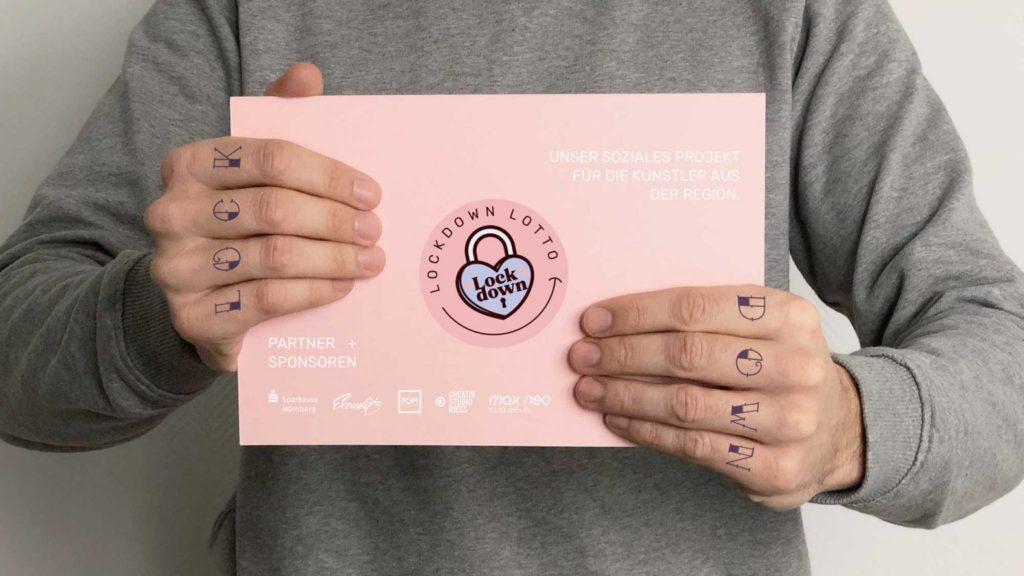 Ein Mann hält eine Karte mit dem Lockdown Lotto Logo hoch