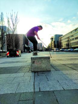 Hier sieht man Hansi beim Skateboardfahren am Kornmarkt in Nürnberg. Hansi grindet dabei mit dem Skateboard auf einem Marmorblock. Dabei hat er einen Blindstock in der Hand. Man sieht dass er sehr schnell fährt.
