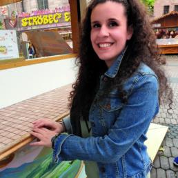 Francesca Di Nato steht vor einer Marktbude am Jakobsplatz in Nürnberg und lächelt in die Kamera.