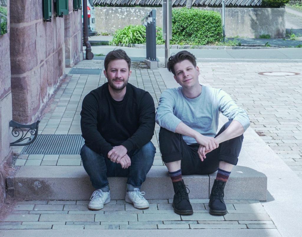 Andreas Jäger und Julian Menz sitzen auf der Treppe vor ihrem Büro