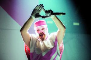 Ein Sänger der Band Deichkind zeigt ein Symbol mit den Händen in die Kamera