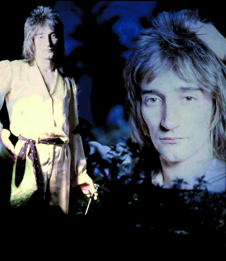 Ein Porträtfoto von Rod Stewart. Er hat hinten und auf der Seite langes blondes Haar. Vorne ein Pony.